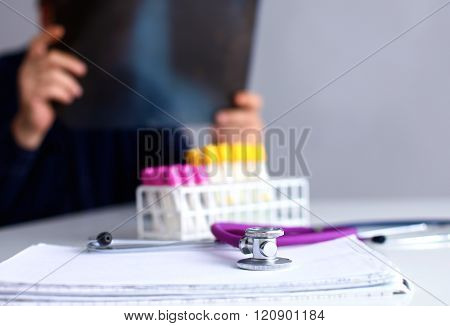 Medical doctor  sitting at table and looking patients roentgen.