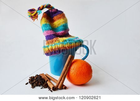 Cup with a knitted hat on, orange, cinnamon and cloves