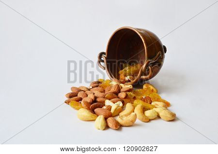 Copper pot with half-spilled nuts and raisins