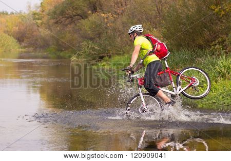 A man crosses the river on a bike on a sunny day.
