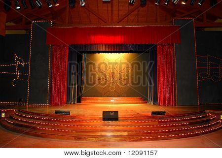 Stage with red curtains and spotlights on the stage floor