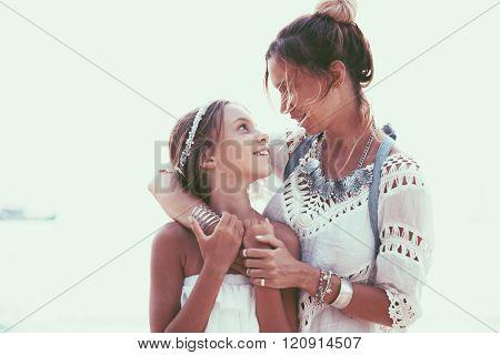 Tween daughter hugging with her mom, boho oriental style