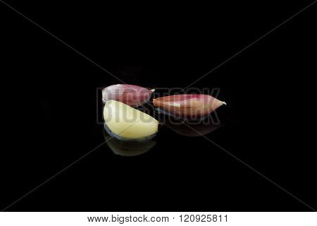 Three wet cloves of garlic on black background