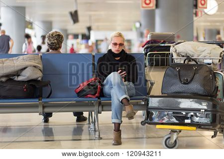 Female traveler using cell phone while waiting on airport.