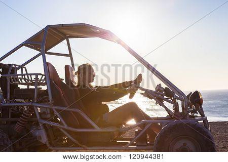 Woman driving quadbike in sunset.