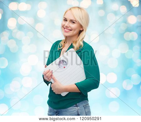 weight loss, diet, slimming, plus size and people concept - smiling young woman holding scales over blue holidays lights background