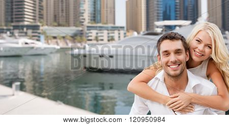 summer holidays, tourism, vacation, travel and dating concept - happy couple having fun over dubai city harbour or waterfront background