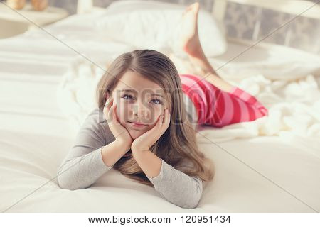 Portrait of a cute little girl, waking up and lying in bed in the morning