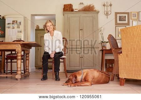 Senior woman smiling confidently in her home with dog