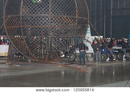 Stuntman drives in steel globe during stunt show