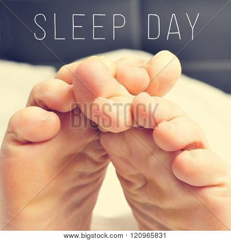 closeup of a young man rubbing his bare feet together in bed and the text sleep day