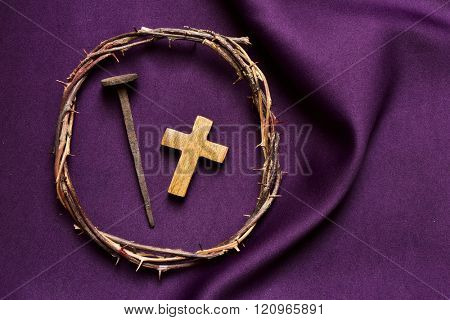 high-angle shot of a wooden christian cross, a rusty nail and the crown of thorns of Jesus Christ, on a purple drapery