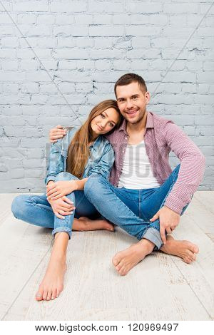 Handsome Man Sitting On The Floor And Embracing His Girlfriend