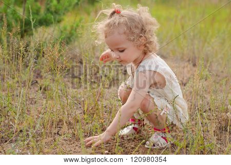 Beautiful Girl Sitting On His Haunches And Learn Something In The Grass