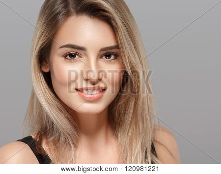 Beautiful Young Woman Smiling Posing With Blond Hair On Gray Background