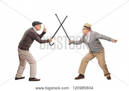 Studio shot of two senior gentlemen having a sword fight with their canes isolated on white background