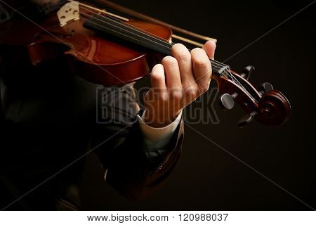 Musician plays violin on black background, close up