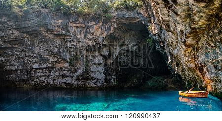 small boat inside a cave lake with blue water in kefallonia greece