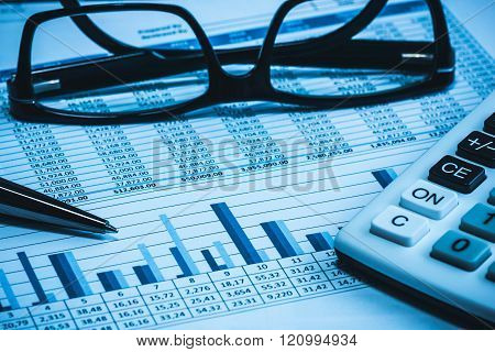 Accounting financial bank banking account stock spreadsheet data with glasses pen and calculator in blue
