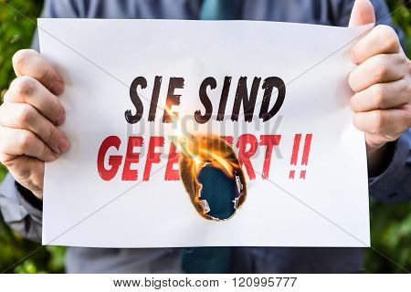 Businessman Is Holding A Burning Paper