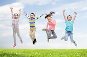 happiness, childhood, freedom, movement and people concept - happy little children jumping in air over blue sky and grass background poster