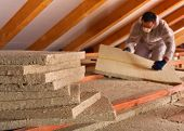 Thermal insulation of a building - mineral wool panels stack with man measuring in the background poster
