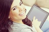 Instagram style portrait of a beautiful happy young Latina Hispanic woman smiling and using a tablet computer or iPad at home on her sofa poster