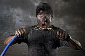 young untrained man joining electrical cable suffering domestic accident with dirty burnt face in funny shock expression screaming crazy in electricity DIY repairs danger concept poster