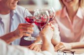Business people are smiling talking and clanging glasses of wine together during business lunch close-up poster