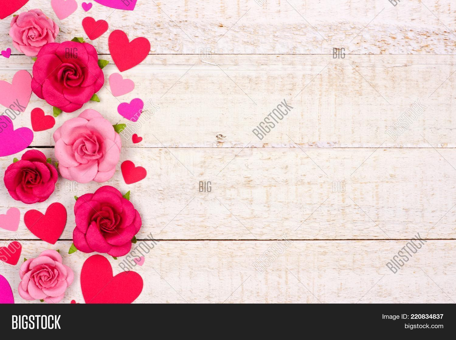Valentines Day Side Border Of Red And Pink Paper Hearts Roses Against A Rustic White