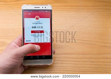 Zhongshan,China-December 26, 2017:Chinese man checking the Alipay red pocket on the mobile.Alibaba sends out lots of free red pockets as gift to users.