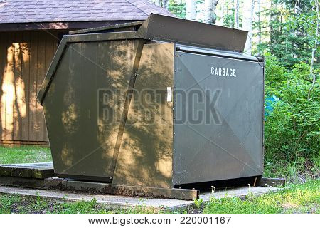 A large garbage bin at a campground.