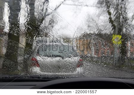 View through a car window of the street. On the street it is raining,drops of a rain flow down on a car window.