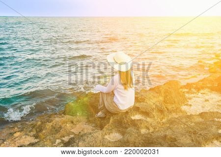 Young Beautiful Woman in Boho Clothes Long Hair Sunhat Sitting on Rocks at Shore Looking at Turquoise Sea Horizon. Golden Sun Flare. Meditation Tranquility Harmony Serenity