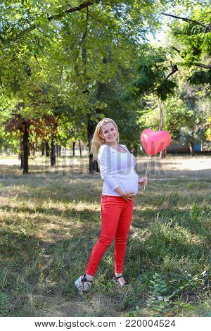 Alluring Future Mother of European Appearance Enjoys Pleasant Things and Look Forward to Appearance of First-Born Into World Photographed For Advertising of Women's Clothing For Pregnant With Pink Ballon in Shape of Heart in Green Sunny Park Outdoors in D