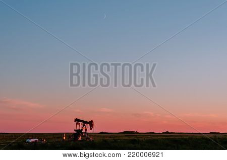 At sunset, oil pumps pour oil on a black field with a pond. Red glow in the background.