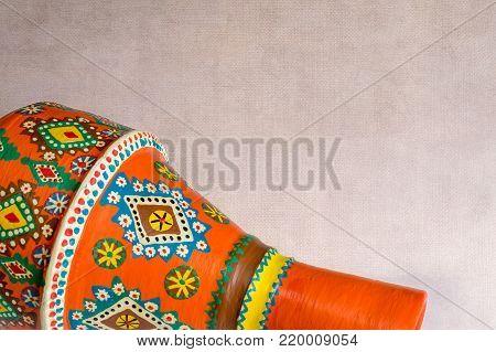 Handmade artistic pained orange pottery vase (arabic: Kolla) over grunge textured background