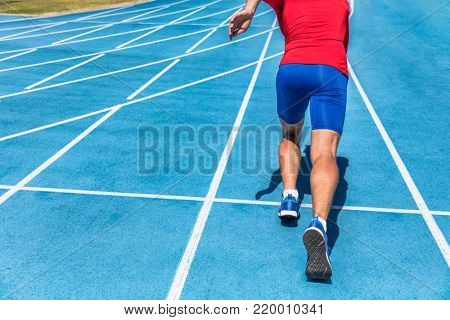 Runner athlete starting running at start of run track on blue running tracks at outdoor athletics and fiel stadium. Sprinter. Sport and fitness man lower body, legs and running shoes sprinting.