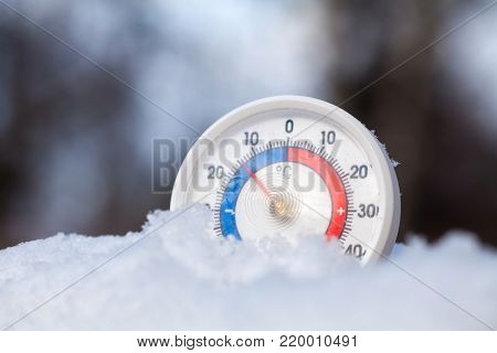 Thermometer with celsius scale placed in a fresh snow showing sub-zero temperature minus fourteen degree a cold winter weather concept