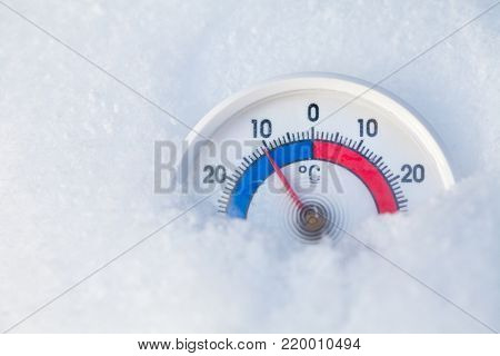 Thermometer with celsius scale placed in a fresh snow showing sub-zero temperature minus eleven degree a cold winter weather concept
