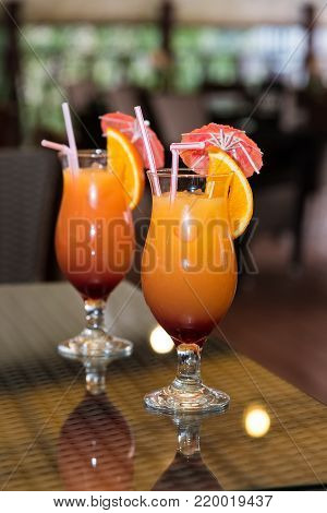 Two orange cocktails with a slice and an umbrella