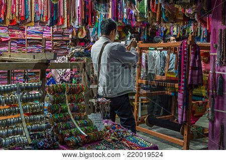POKHARA, NEPAL - September 29, 2013: Tourists buying souvenirs in a shop. Original regional jewelery from Nepal. Pokhara streets.