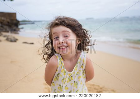 Lifestyle portrait of a young three year old girl playing on the beach in Oahu Hawaii.