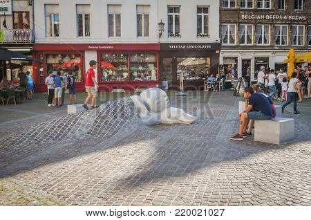 ANTWERP, BELGIUM. July 17, 2017. Child playing on a statue of a boy Nello and his dog Patrasche by the Antwerp Cathedral. They are characters of a novel