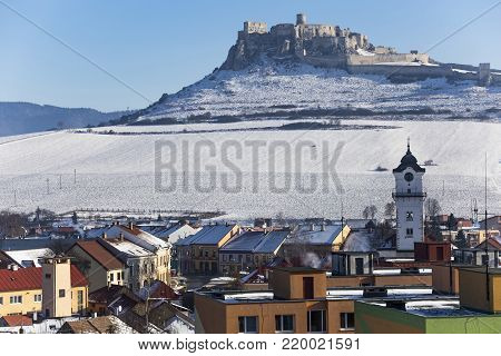View of the snow-covered Spis Castle ( Spissky hrad)  , the largest castle in Slovakia from the town of Spisske Podhradie, against a blue sky at winter day. Slovak National Cultural Monument. UNESCO World Heritage Site. Tourist attraction