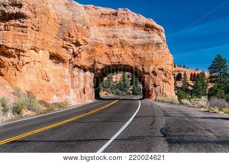 Arch tunnel through rock along scenic highway 12 near Red Canyon. Utah