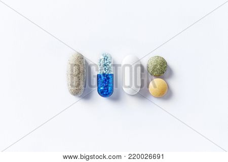 Dietary supplements and vitamins on white background