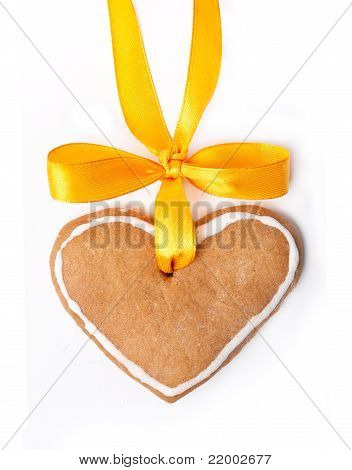 Ginger bread heart and yellow bow on white