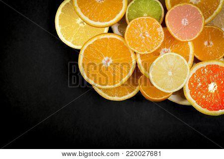 Citrus fruits (orange, lemon, grapefruit, mandarin, lime) on the dark background. Fruit food background. Fresh citrus fruit assortment