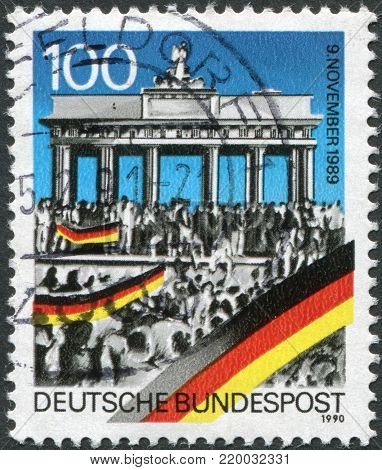GERMANY - CIRCA 1990: A stamp printed in Germany, is dedicated to the first anniversary of the fall of the Berlin Wall shows people around the Brandenburg Gate, circa 1990